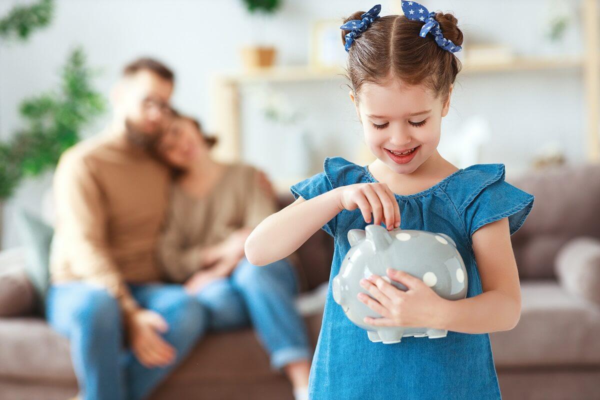 dítě vkladá do pokladničky peníze